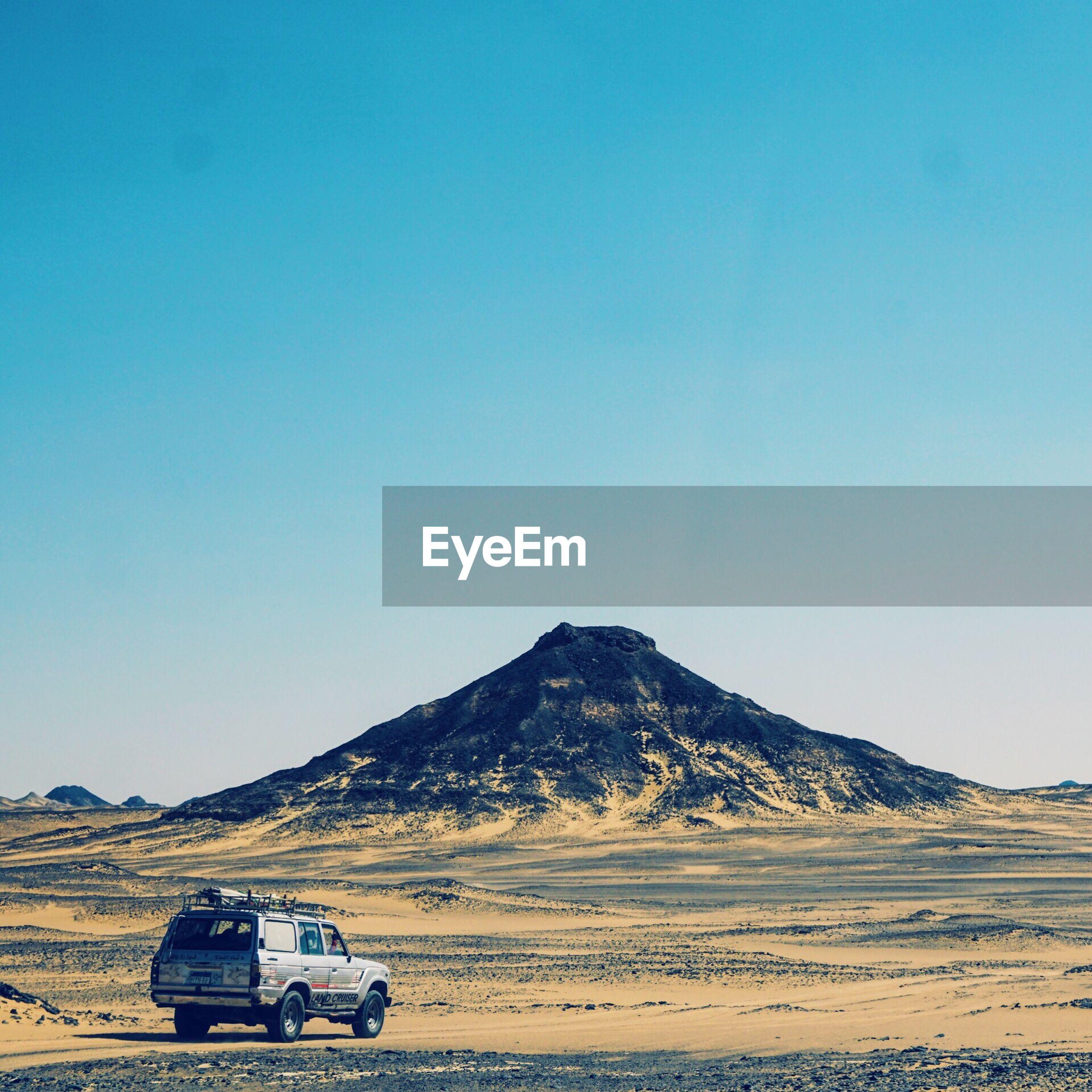 CAR ON DESERT AGAINST BLUE SKY