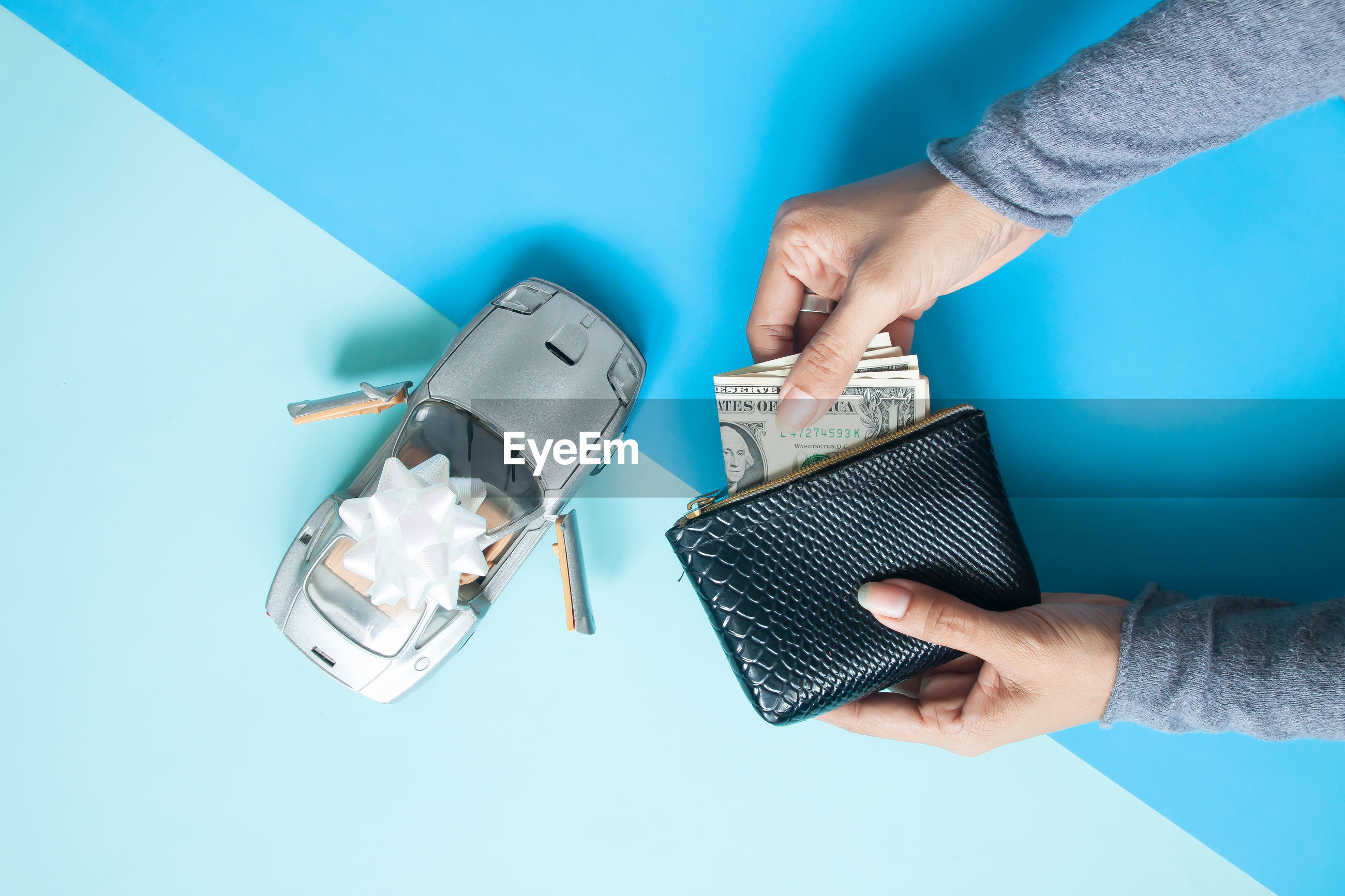 Cropped hands holding paper currency in purse against blue background