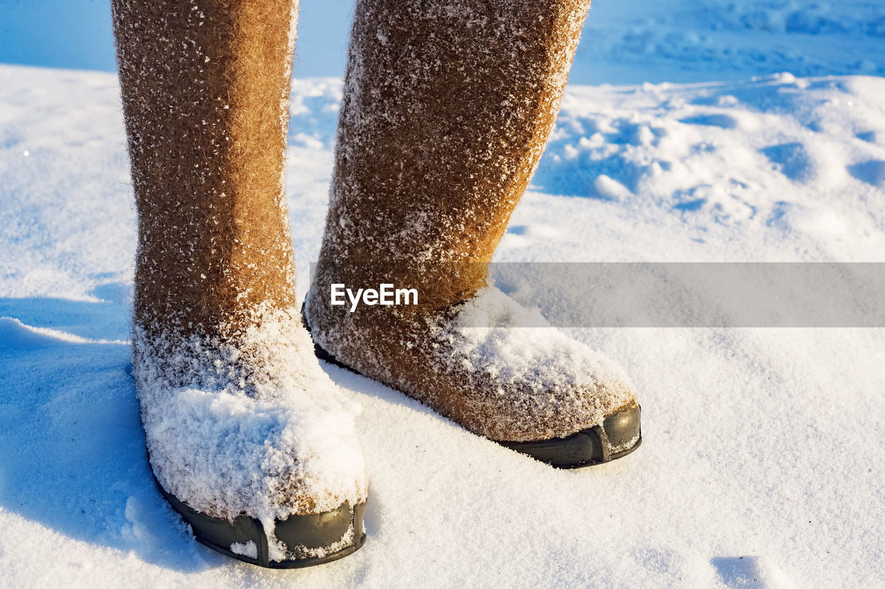 Rubber boots on snow covered field during sunny day