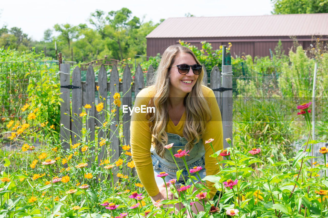 Smiling young woman standing by plants