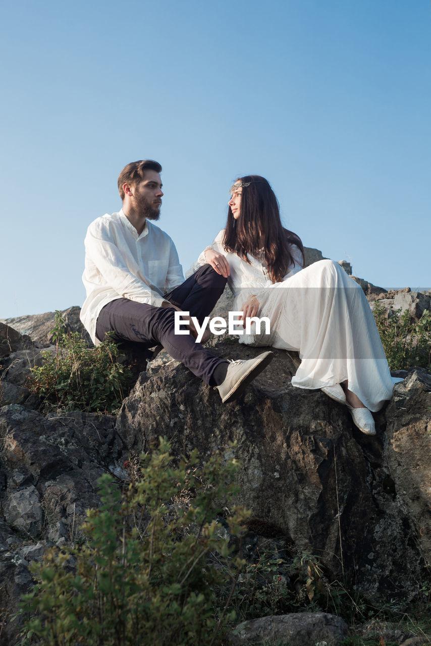 Romantic couple sitting on mountain against sky