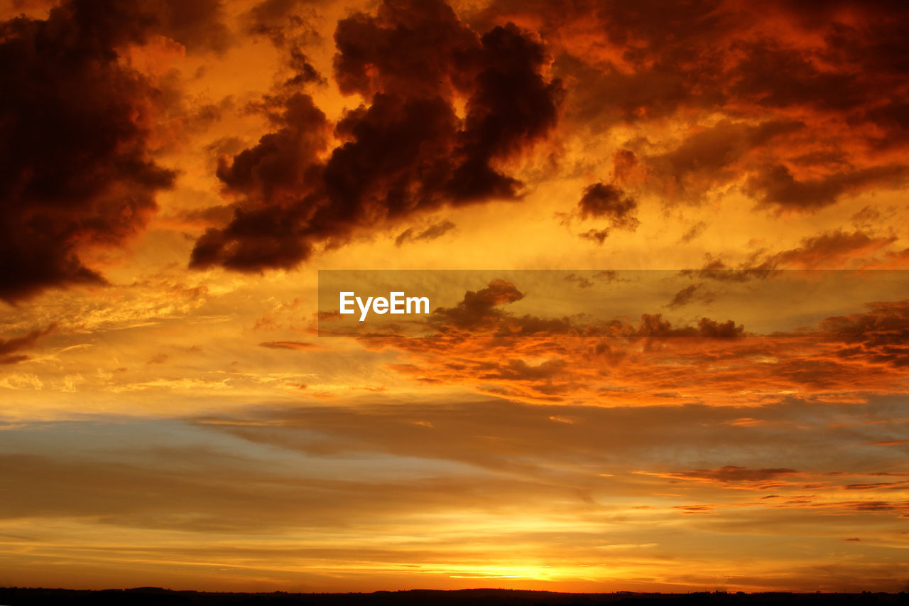 sky, cloud - sky, sunset, scenics - nature, beauty in nature, orange color, tranquil scene, tranquility, idyllic, dramatic sky, nature, no people, low angle view, backgrounds, outdoors, majestic, cloudscape, non-urban scene, overcast, meteorology, romantic sky