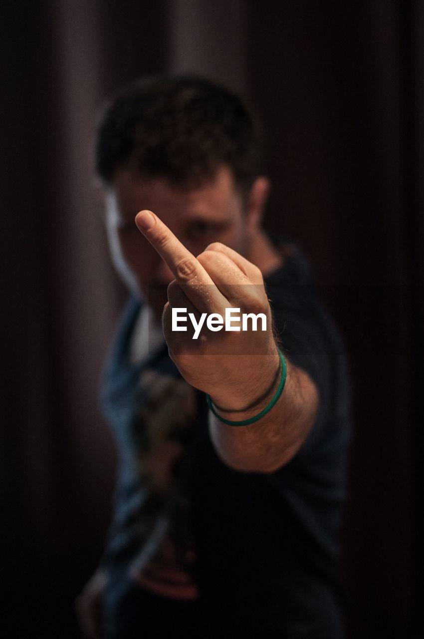 Man showing obscene gesture while standing in darkroom