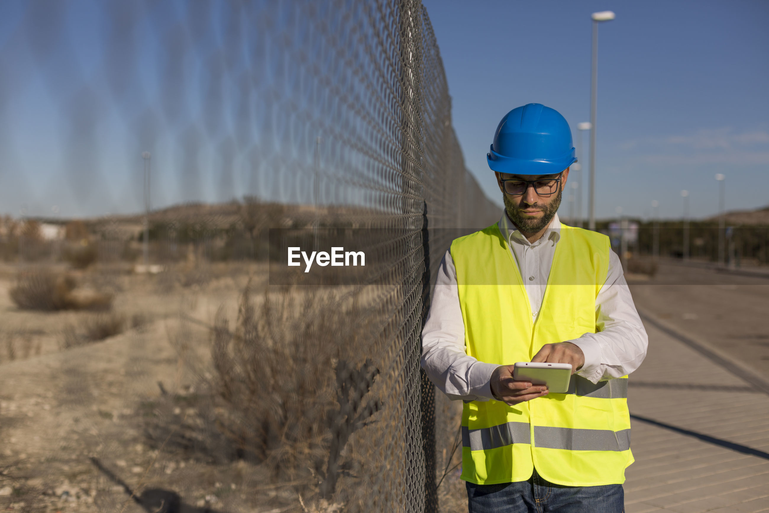 Engineer using digital tablet standing by chainink fence at construction site