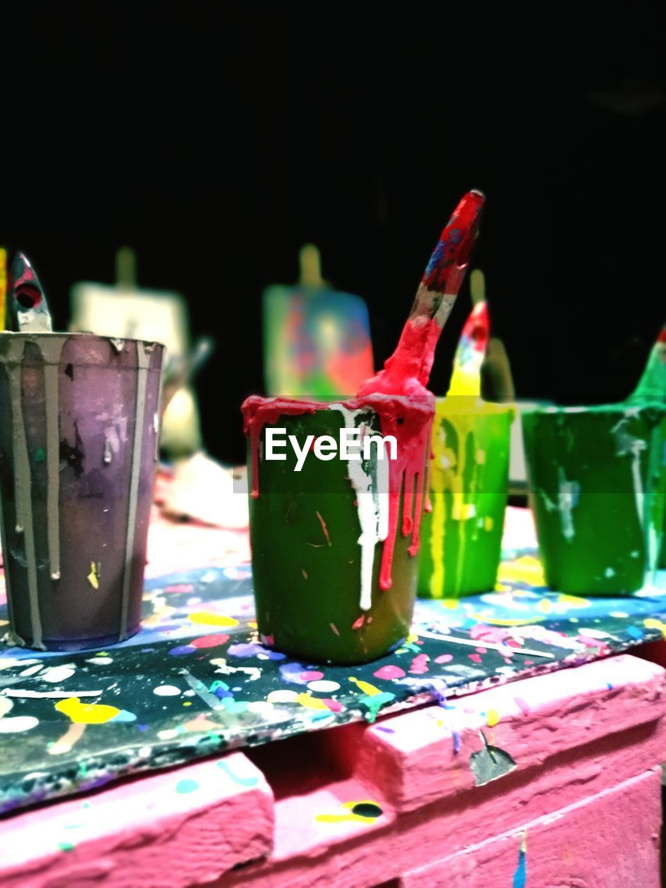 Close-Up Of Paints In Containers With Paintbrushes At Workshop