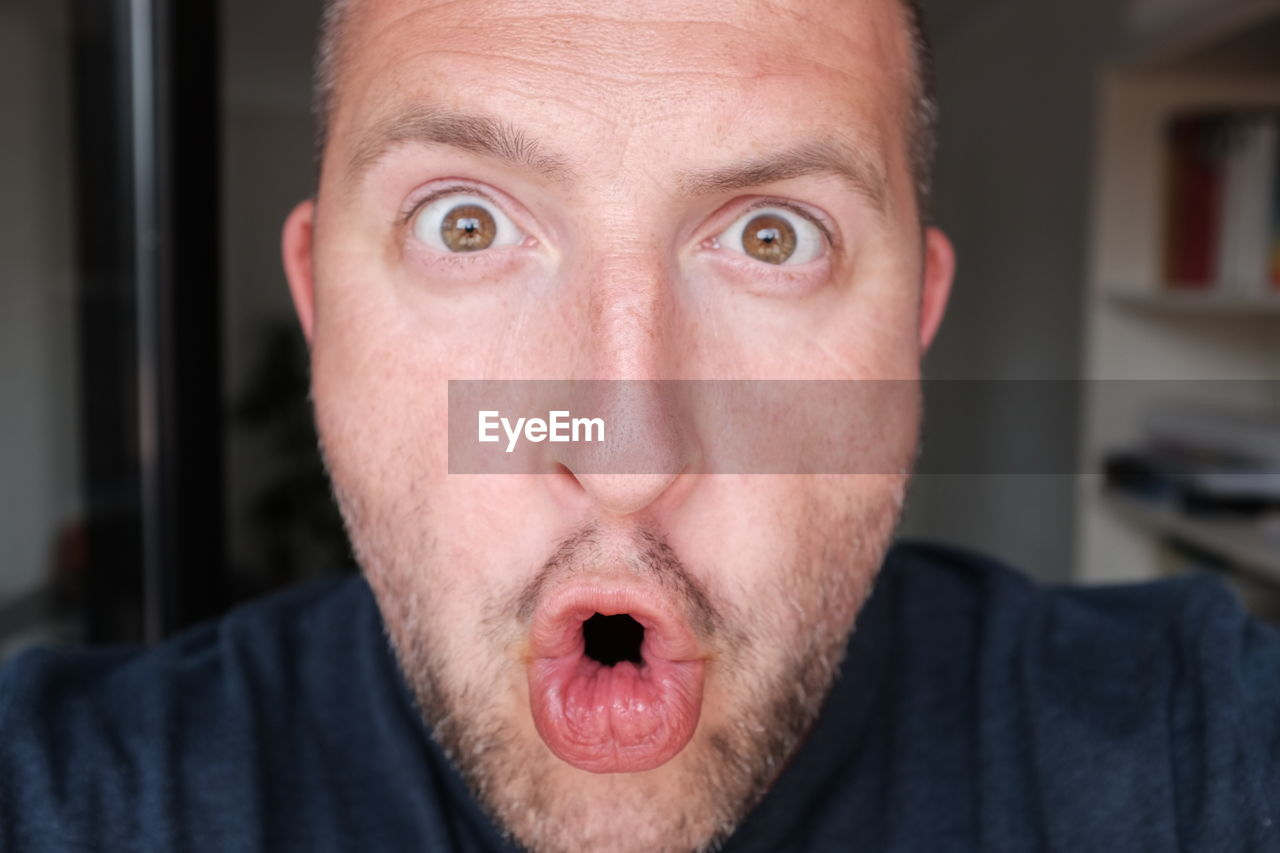 Close-up portrait of shocked man at home
