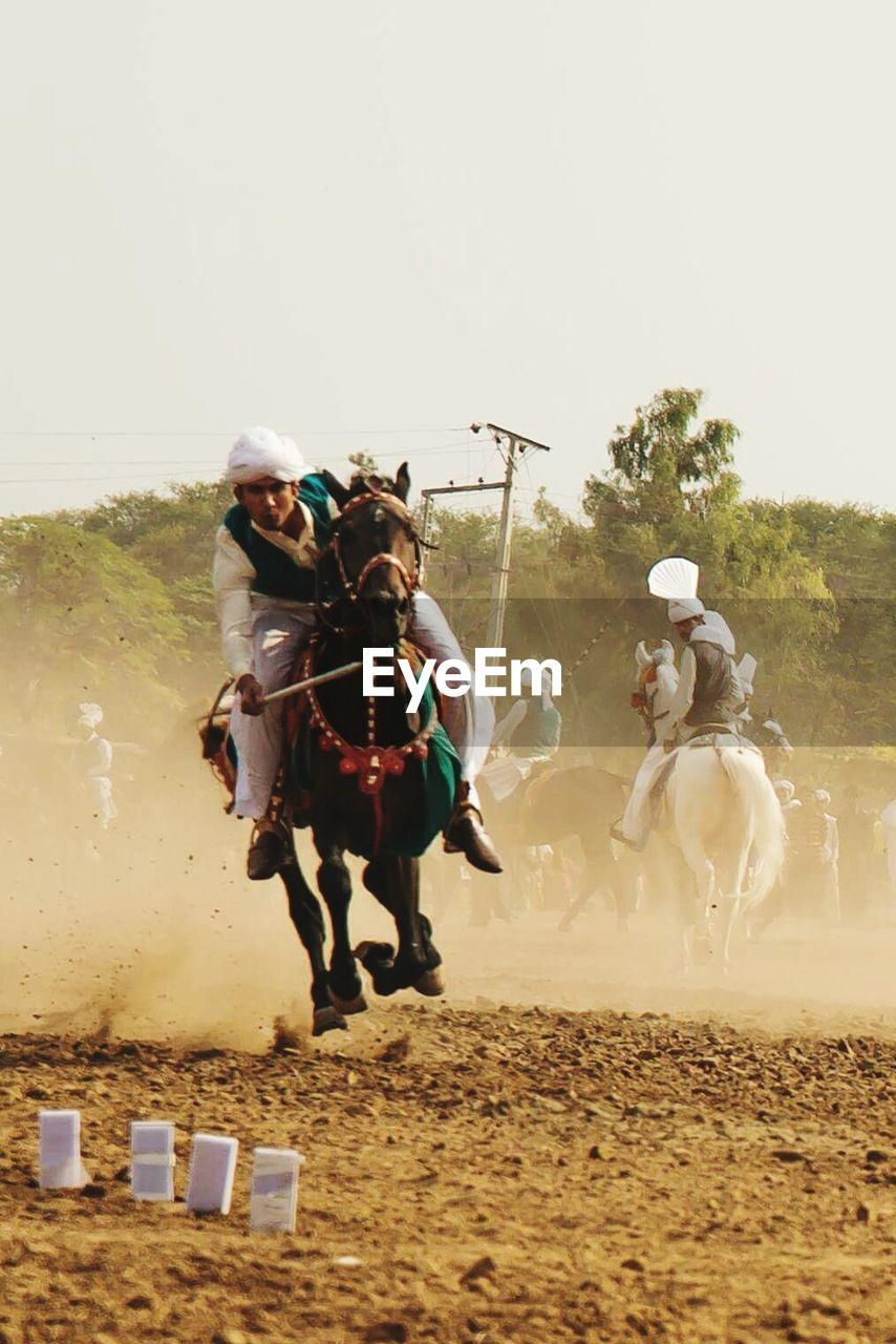 horse, domestic animals, field, real people, dust, mammal, adventure, horseback riding, competition, tree, jockey, outdoors, livestock, day, full length, riding, sand, sky, lifestyles, motion, helmet, men, clear sky, sports race, horse racing, headwear, young adult, adult, people