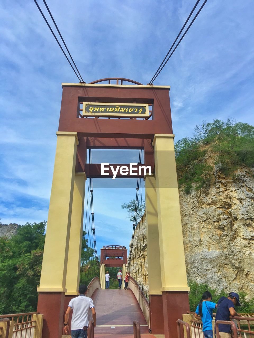 sky, architecture, real people, day, nature, built structure, transportation, text, communication, cloud - sky, sign, western script, tree, plant, incidental people, lifestyles, people, connection, outdoors, bridge
