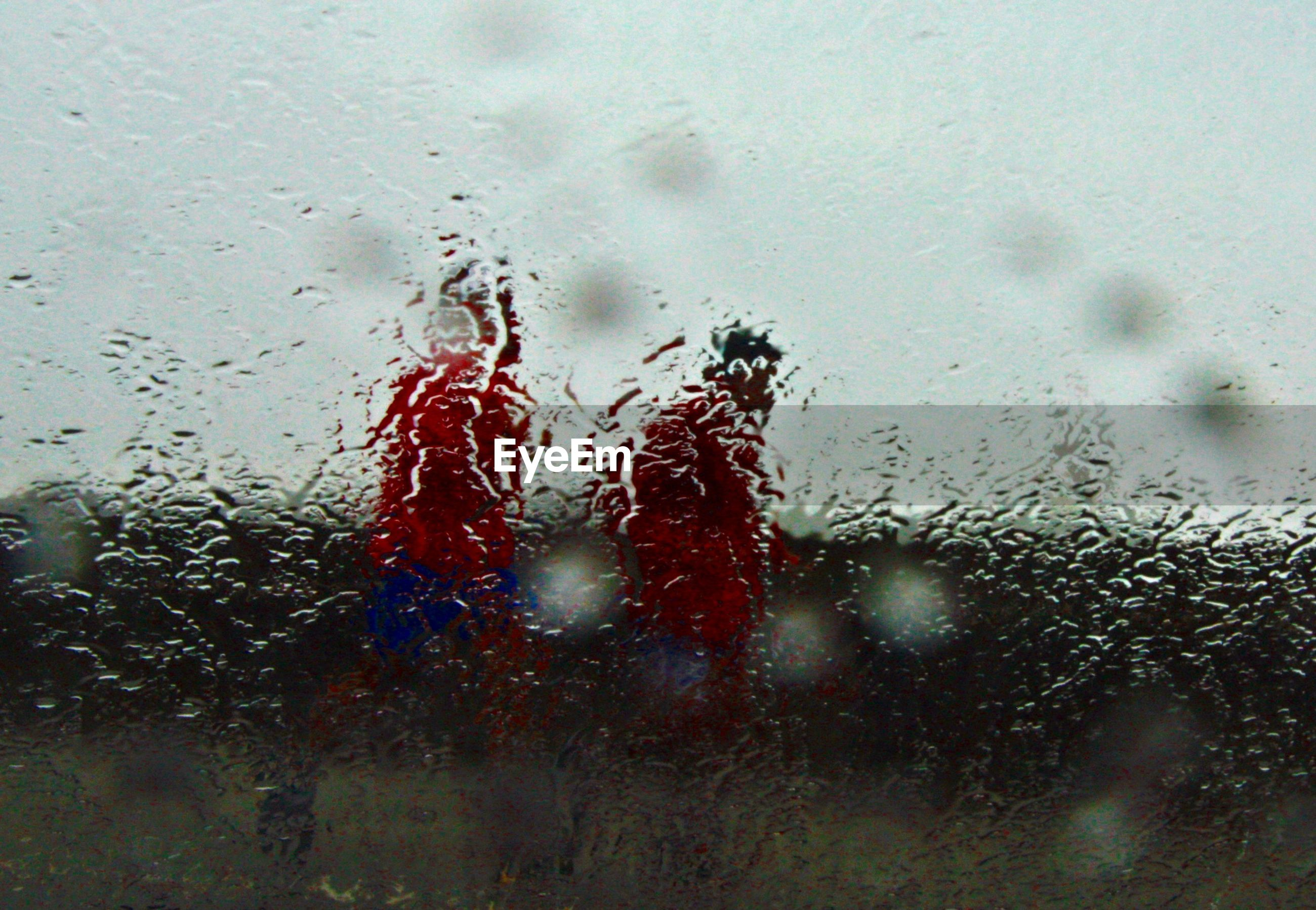 Men walking on field seen through wet window in rainy season