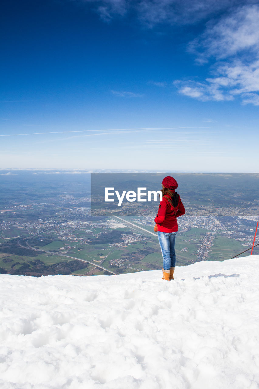 Rear view of woman standing on snow covered mountain