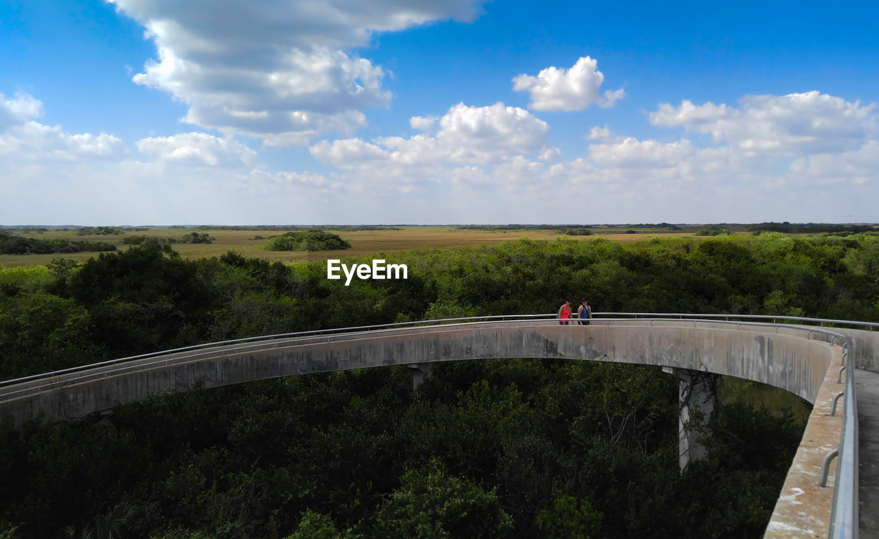 Man Standing At Observation Tower Against Cloudy Sky