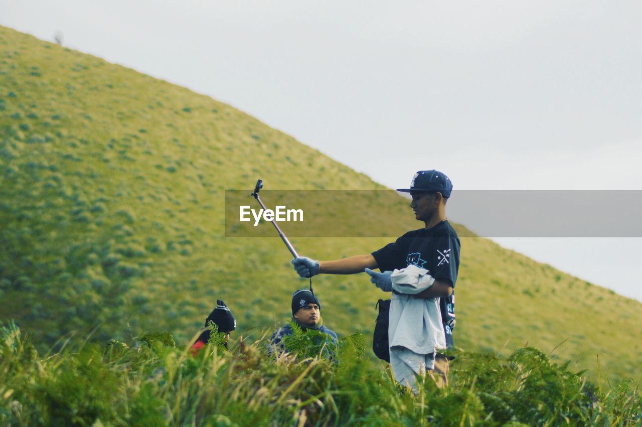 REAR VIEW OF MEN ON FIELD