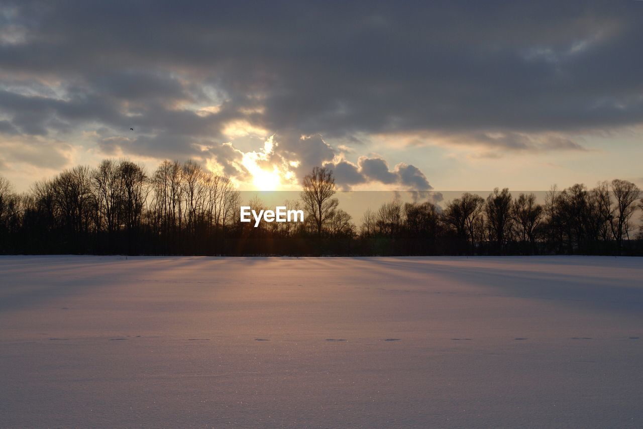 sunset, cold temperature, scenics, tranquility, nature, winter, beauty in nature, cloud - sky, tranquil scene, sky, tree, snow, no people, outdoors, sunlight, landscape, bare tree, day