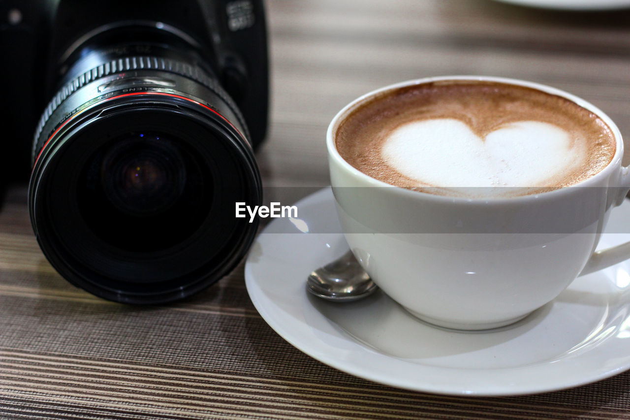 drink, refreshment, cup, crockery, table, mug, food and drink, coffee cup, coffee, coffee - drink, still life, photography themes, close-up, no people, camera - photographic equipment, saucer, indoors, frothy drink, technology, lens - optical instrument, digital camera