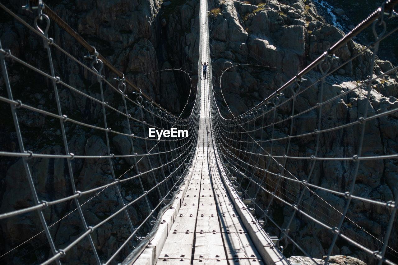 Mature Man Walking On Footbridge Over Mountain