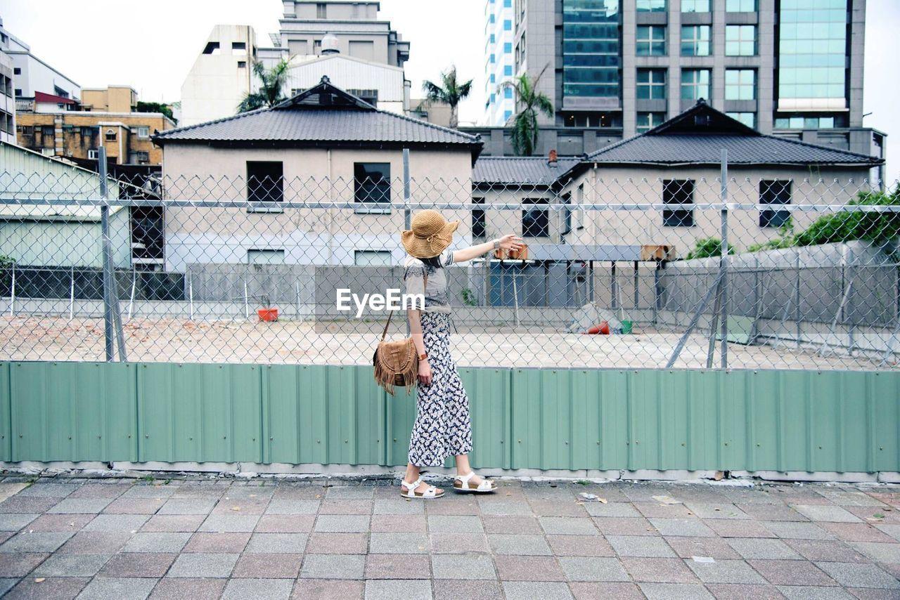 Woman Walking By Fence