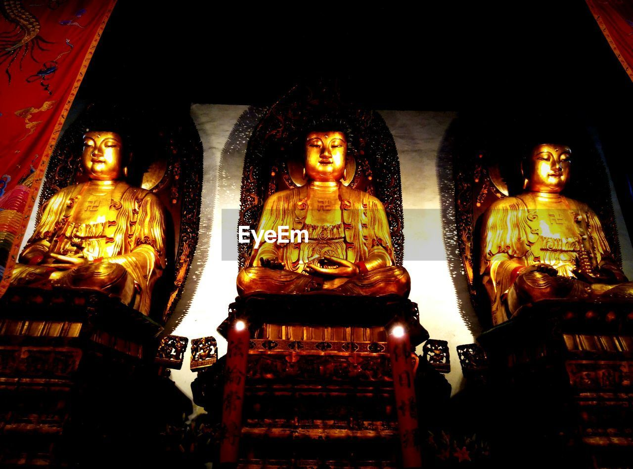 statue, human representation, low angle view, spirituality, religion, sculpture, male likeness, art and craft, golden color, idol, place of worship, gold colored, indoors, no people, golden, architecture, night