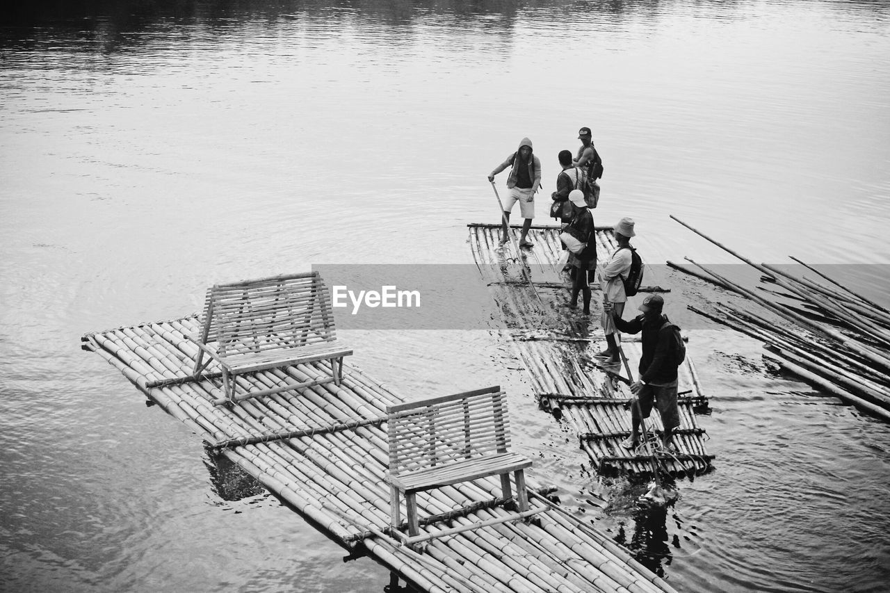 High angle view of men standing on wooden raft