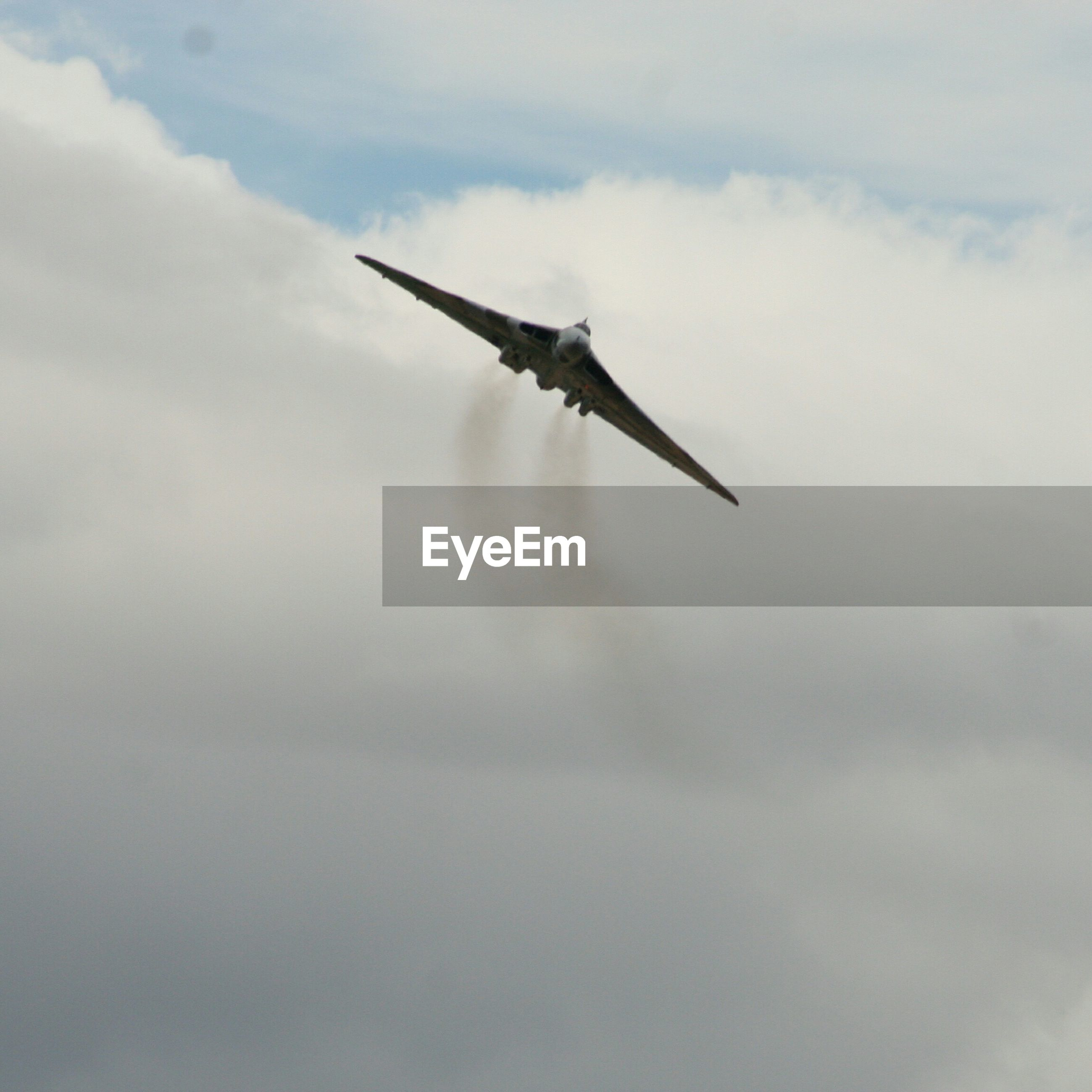 Low angle view of avro vulcan flying against cloudy sky