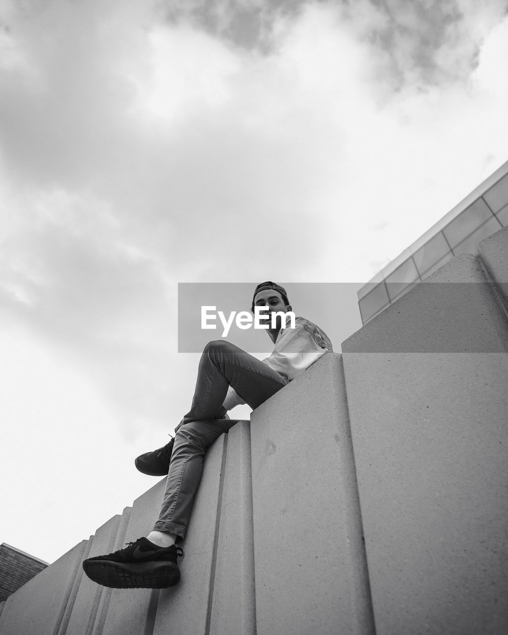 Low angle view of young man sitting on wall against sky
