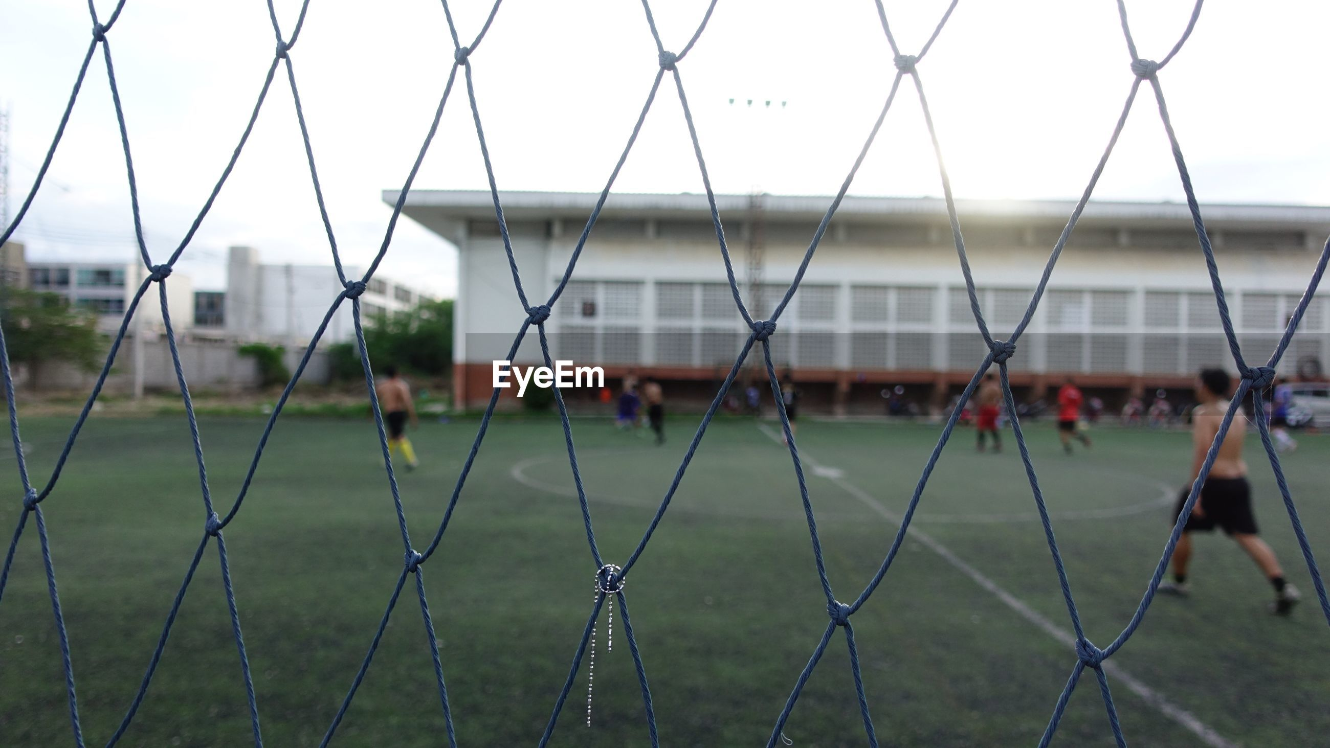 People playing soccer seen through fence