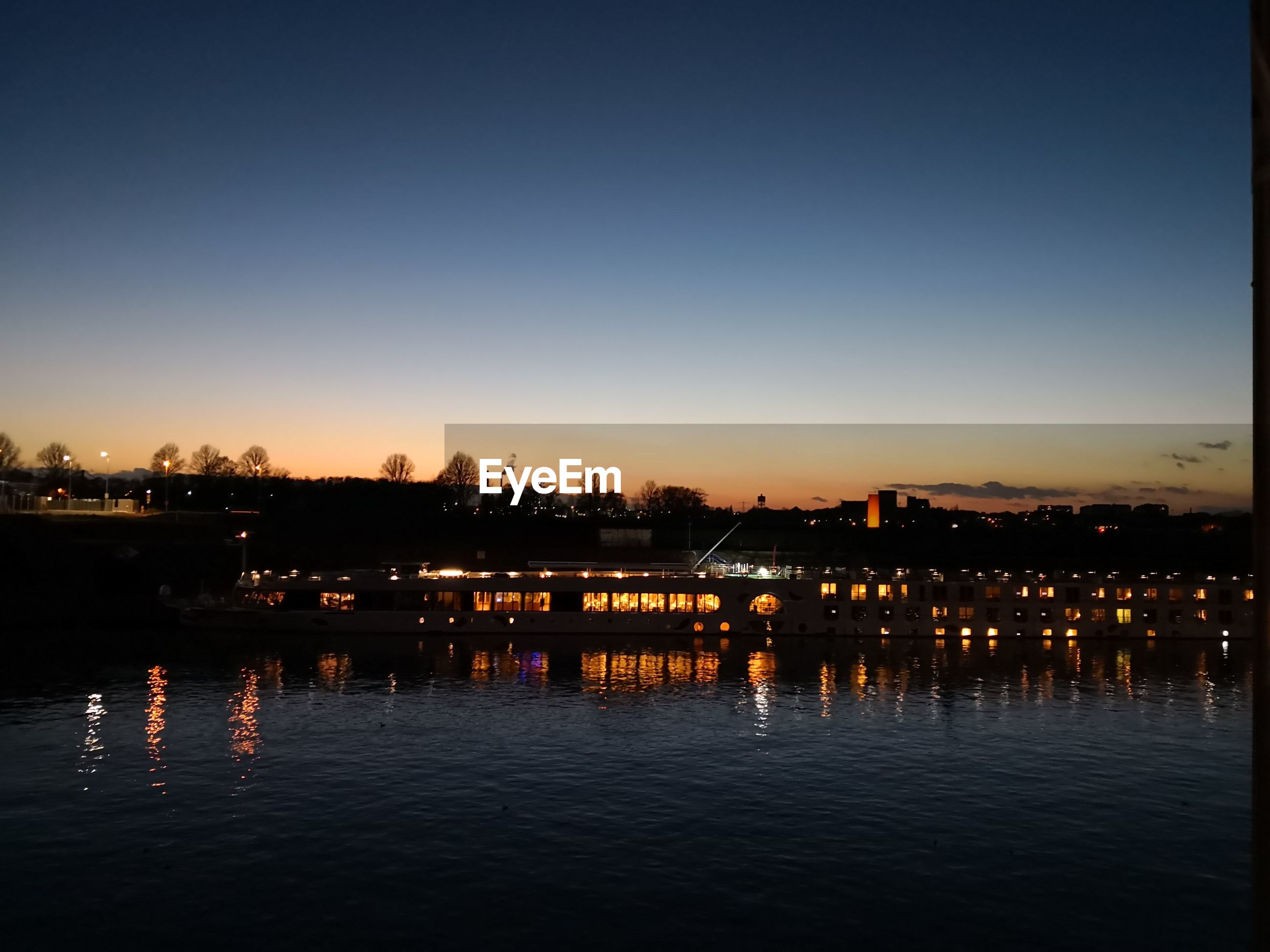 ILLUMINATED CITY BY RIVER AGAINST SKY DURING SUNSET
