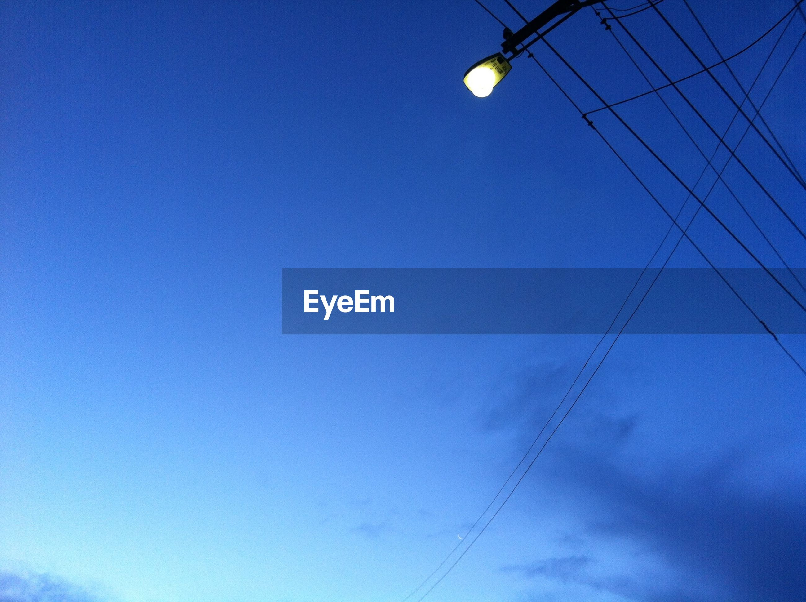 low angle view, electricity, power line, moon, clear sky, blue, cable, connection, power supply, lighting equipment, sky, copy space, electricity pylon, street light, technology, fuel and power generation, electric light, outdoors, dusk, no people