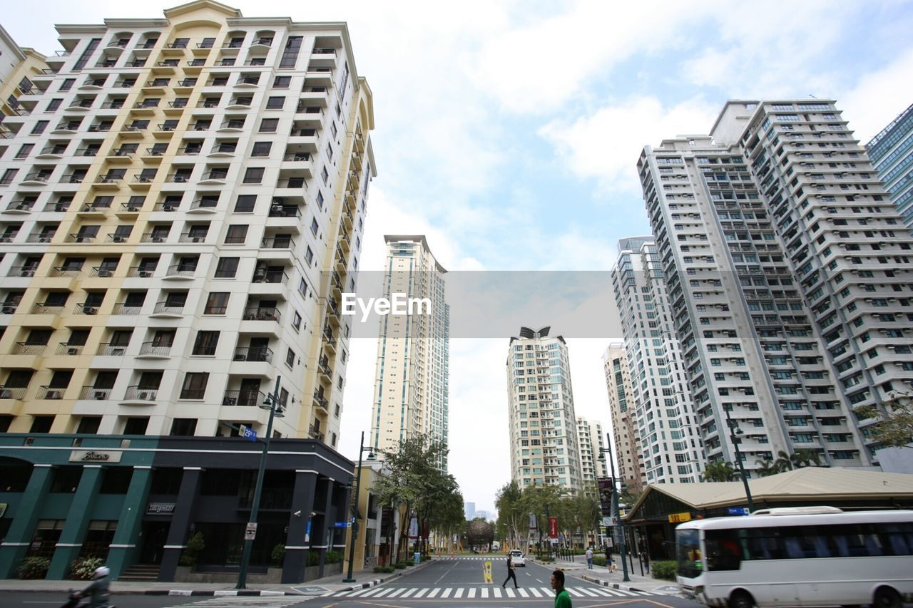 architecture, building exterior, city, skyscraper, built structure, sky, car, day, city life, low angle view, outdoors, road, modern, no people, tree, cityscape