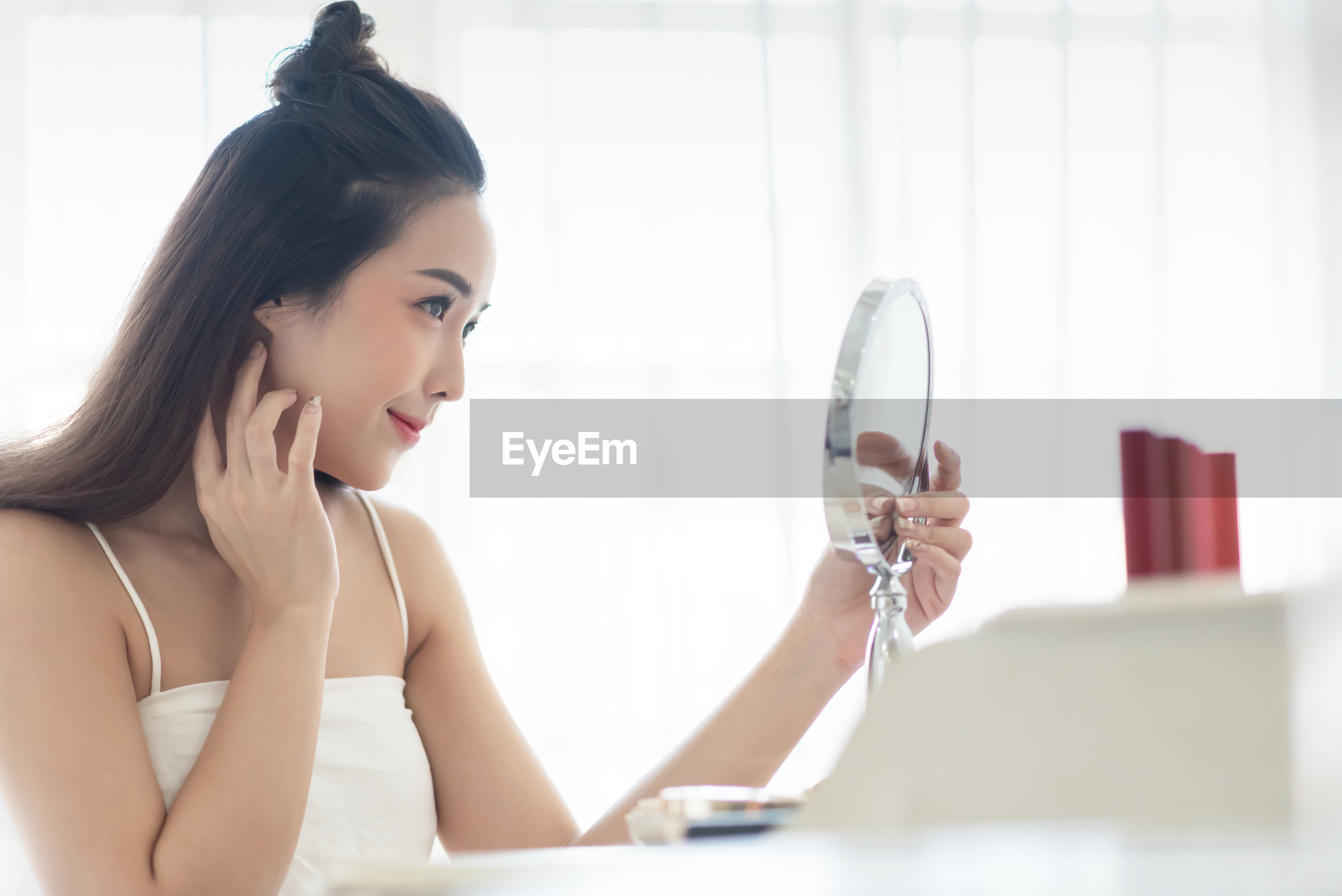 Beautiful woman looking at mirror while sitting at home