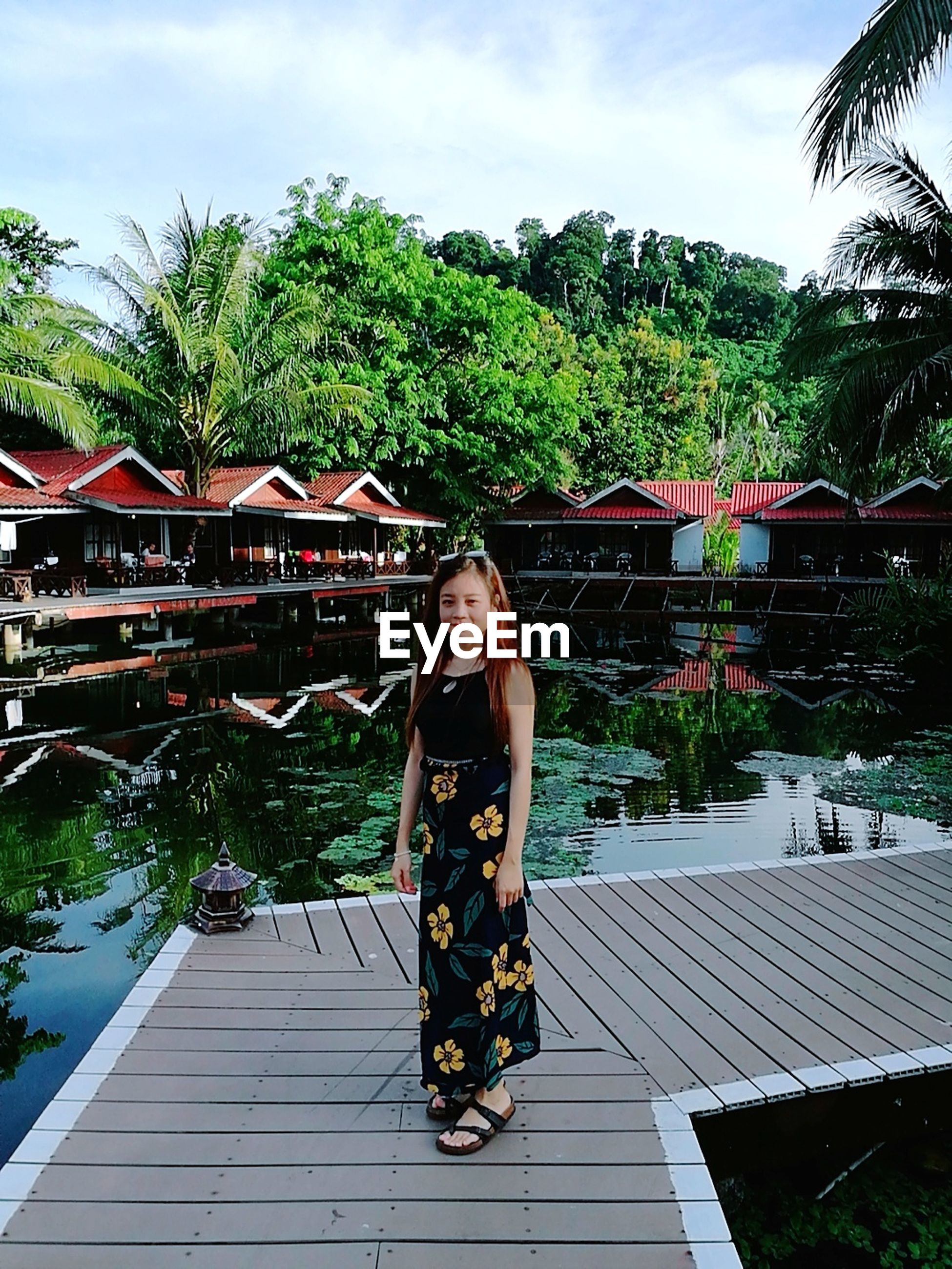 one person, young adult, full length, young women, real people, leisure activity, outdoors, front view, tree, architecture, day, built structure, sky, looking at camera, lifestyles, building exterior, beautiful woman, portrait, water, nature, people