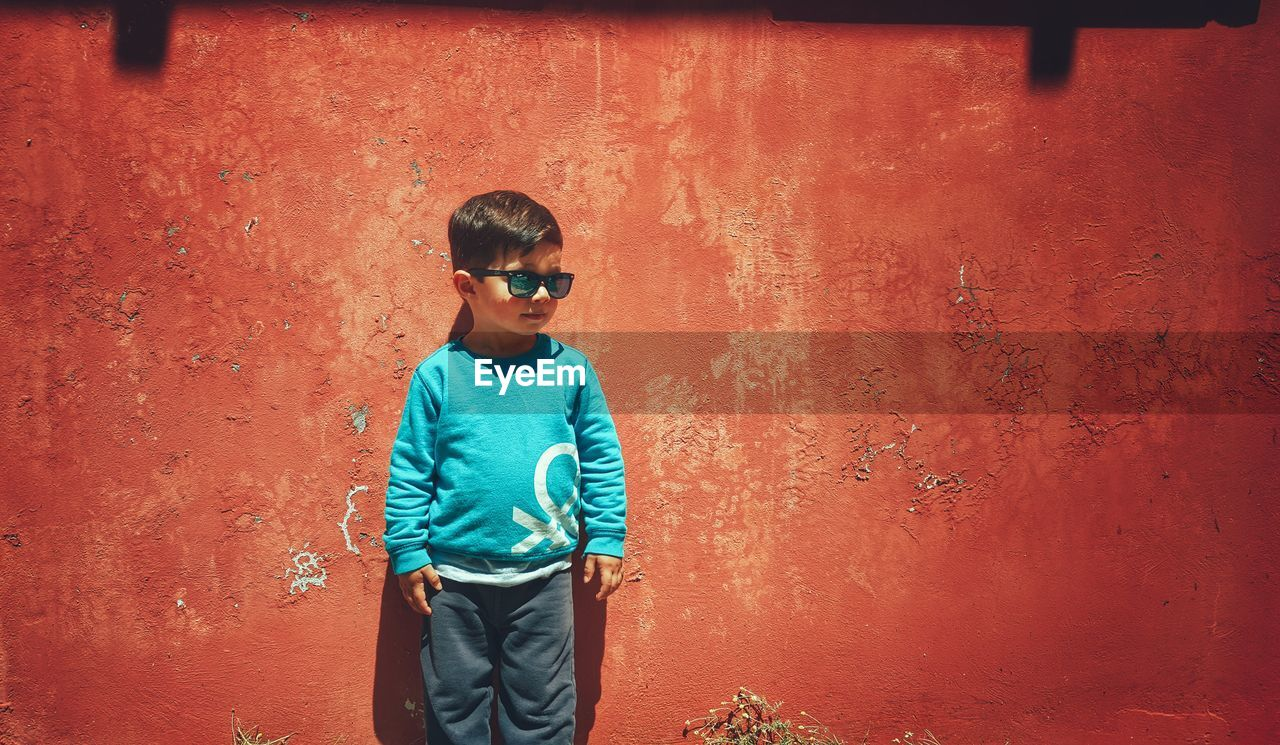 wall - building feature, one person, casual clothing, standing, glasses, real people, lifestyles, three quarter length, males, front view, sunglasses, leisure activity, boys, child, men, fashion, childhood, outdoors, innocence