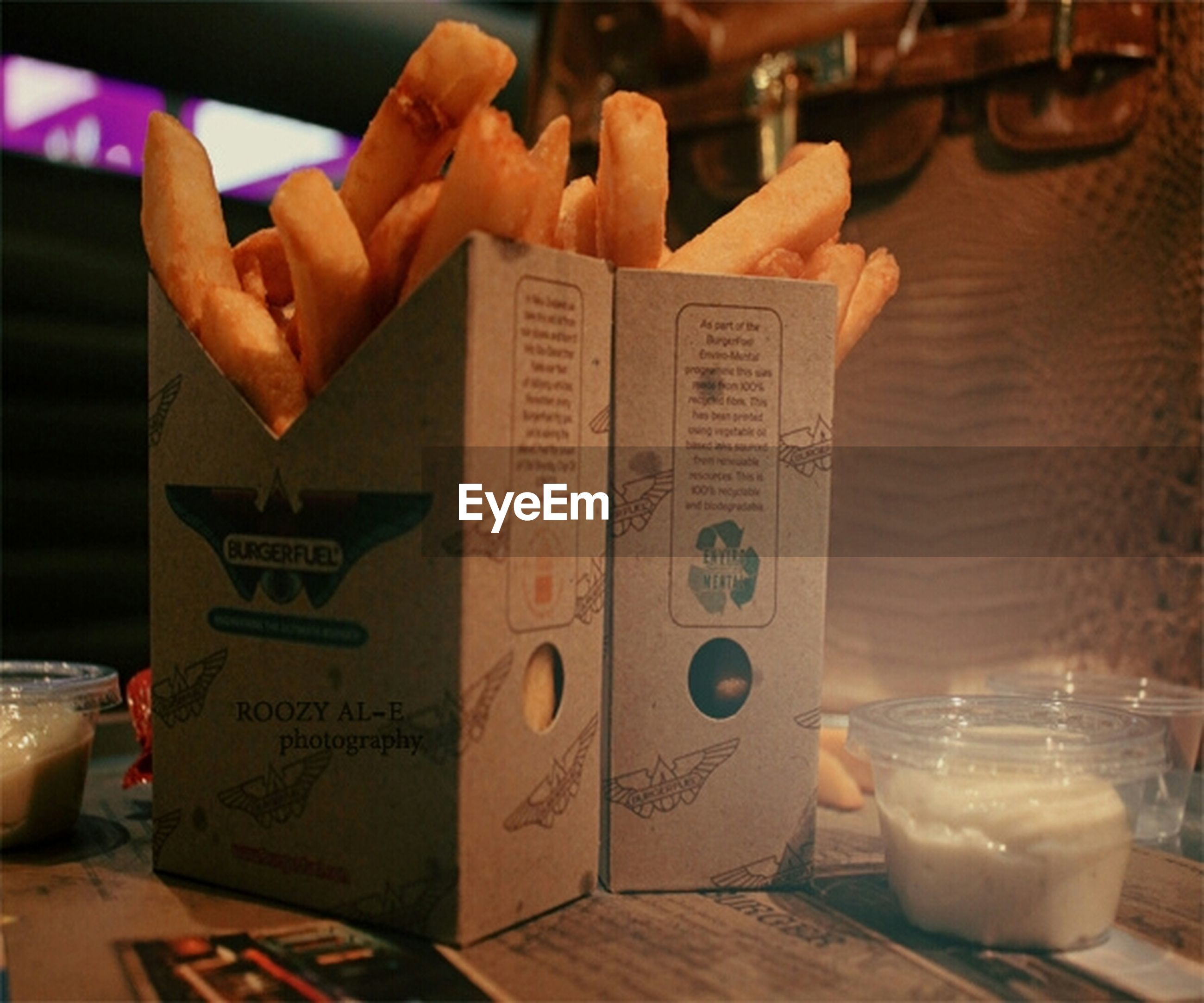 text, indoors, western script, communication, person, paper, non-western script, close-up, table, part of, focus on foreground, holding, food and drink, art and craft, art, creativity, human finger