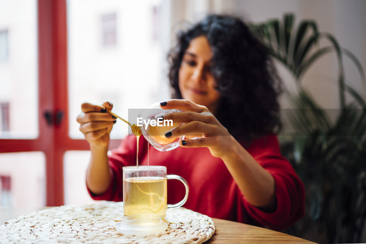 MIDSECTION OF A WOMAN DRINKING GLASS ON TABLE