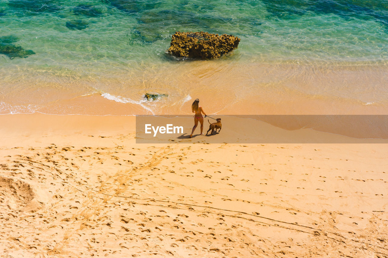 water, land, sand, sea, beach, real people, motion, beauty in nature, nature, day, people, lifestyles, leisure activity, men, scenics - nature, high angle view, tranquility, full length, outdoors