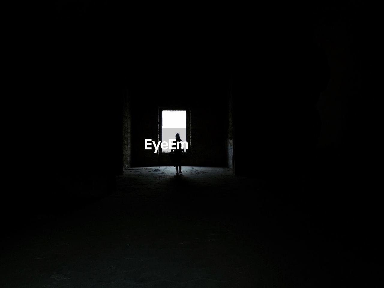 Silhouette woman walking towards light in old building