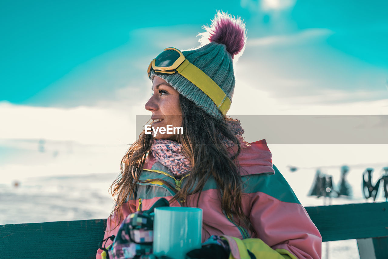Woman Looking Away While Standing Against Sky During Winter