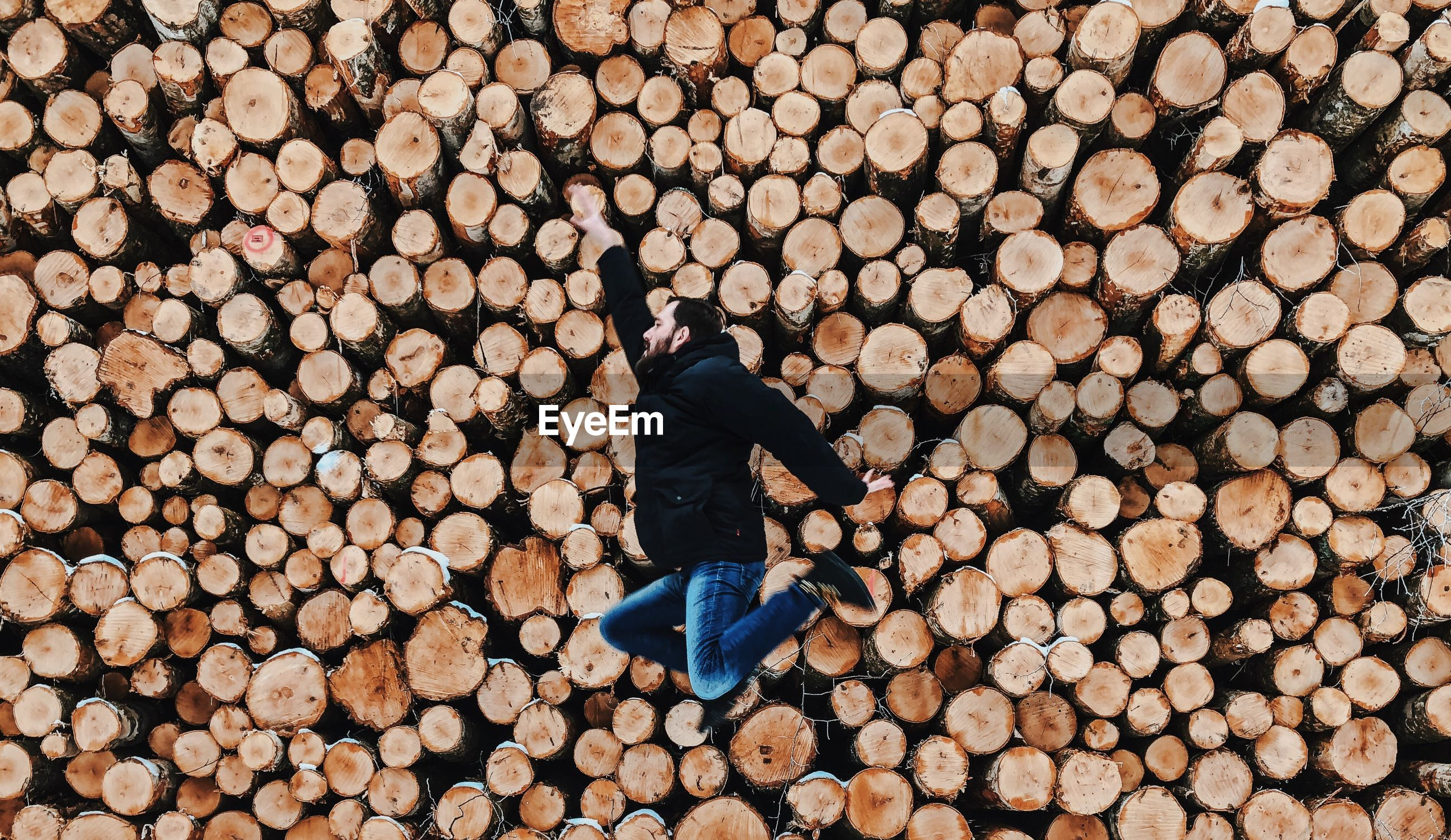 Side view of mid adult man jumping against logs