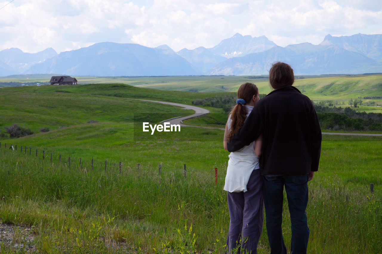 Rear View Of Couple Standing On Grassy Field