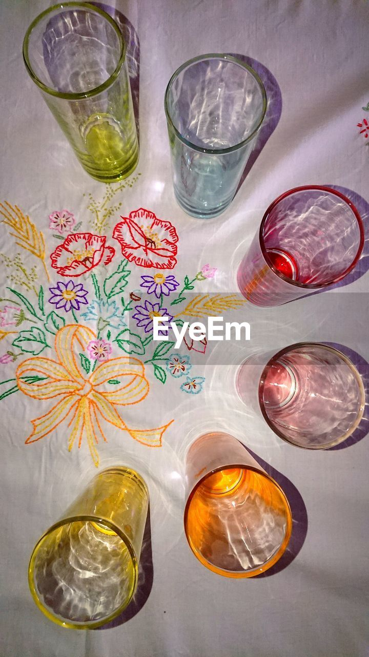 glass, drinking glass, indoors, no people, table, high angle view, still life, household equipment, drink, glass - material, food and drink, refreshment, directly above, close-up, transparent, choice, water, citrus fruit, variation