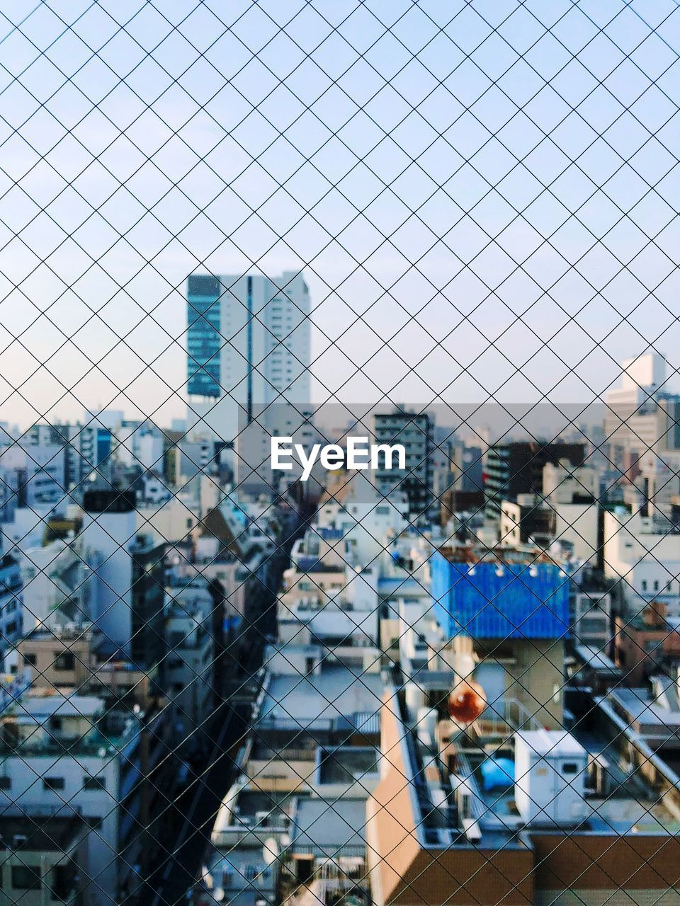 High angle view of city against sky seen through chainlink fence