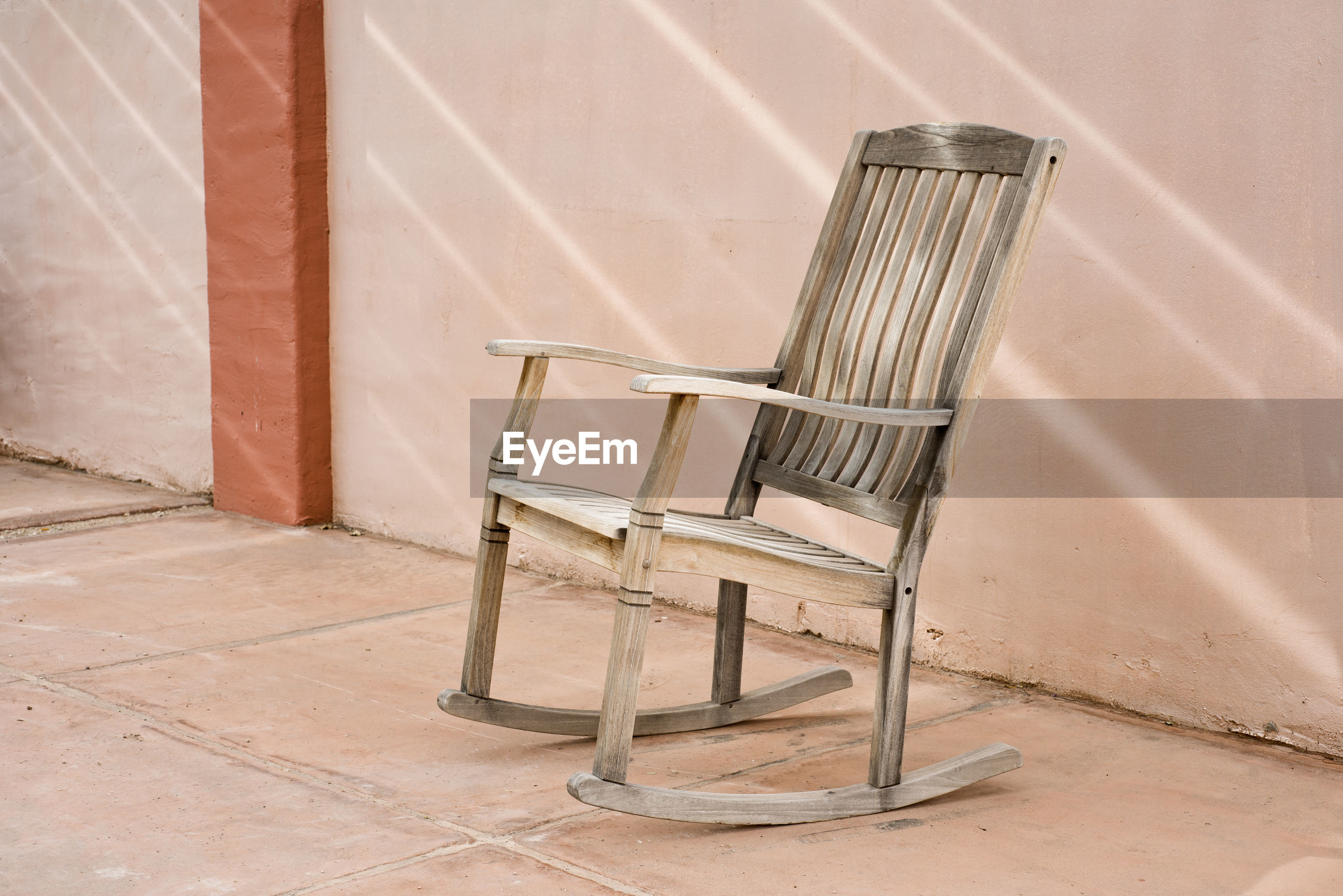 Wooden chair on floor against wall