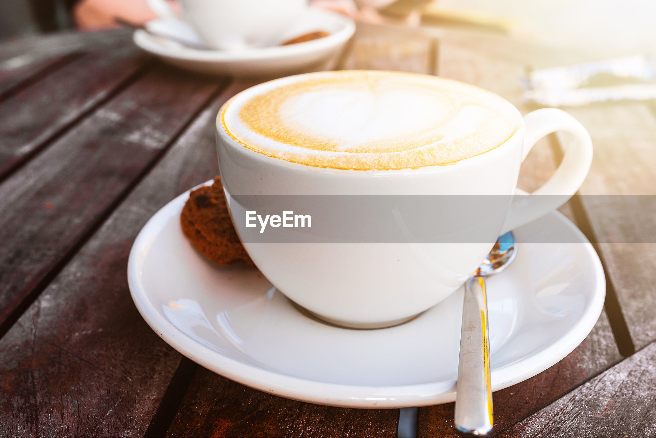 High angle view of cappuccino with cookie served on wooden table
