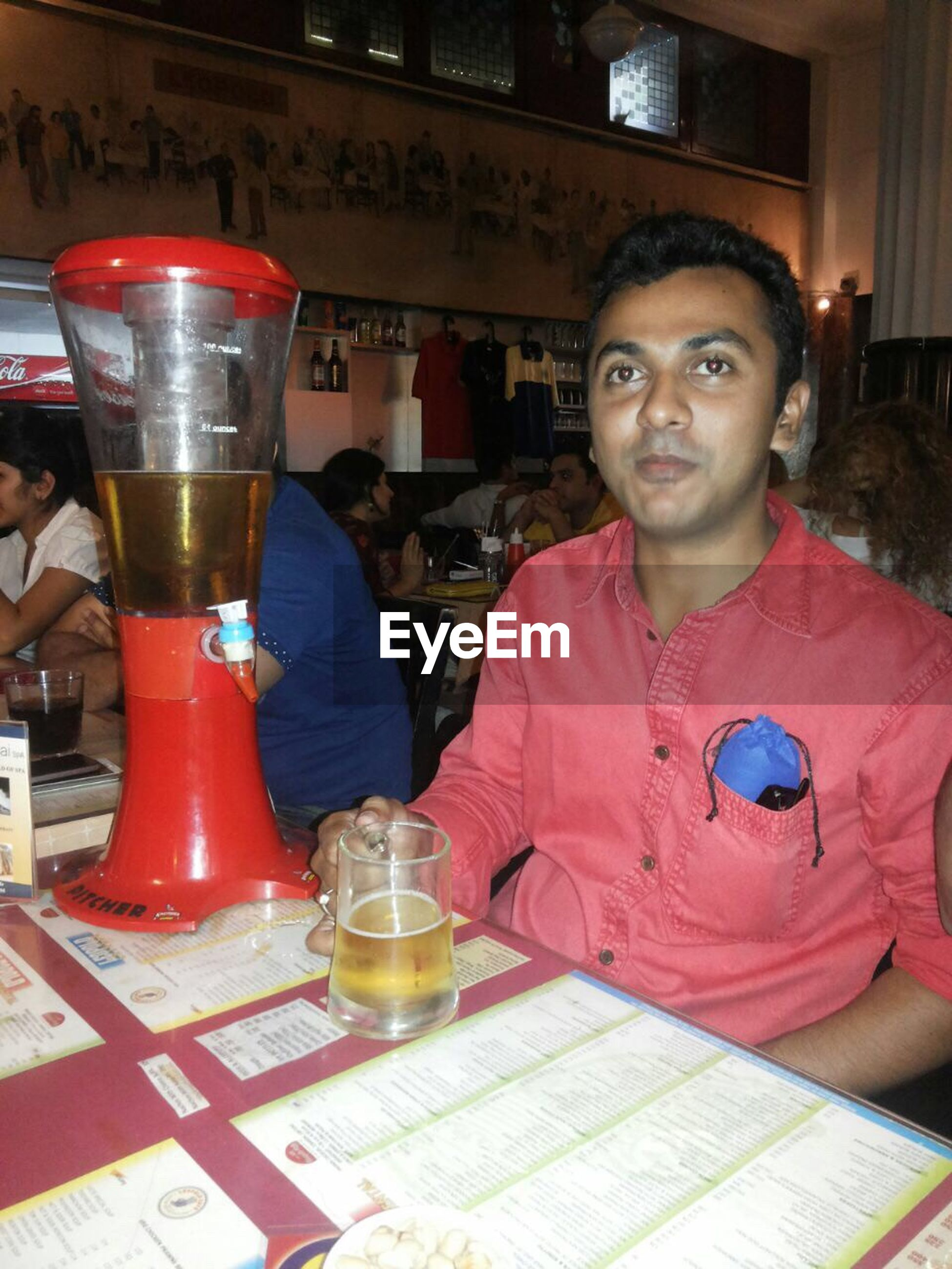 indoors, drink, lifestyles, food and drink, casual clothing, table, leisure activity, person, refreshment, sitting, restaurant, looking at camera, front view, portrait, smiling, glass - material, drinking glass