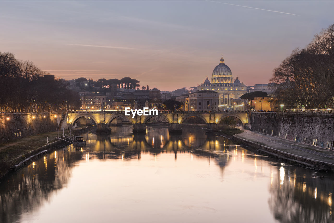 Illuminated berlin cathedral by river against sky during sunset