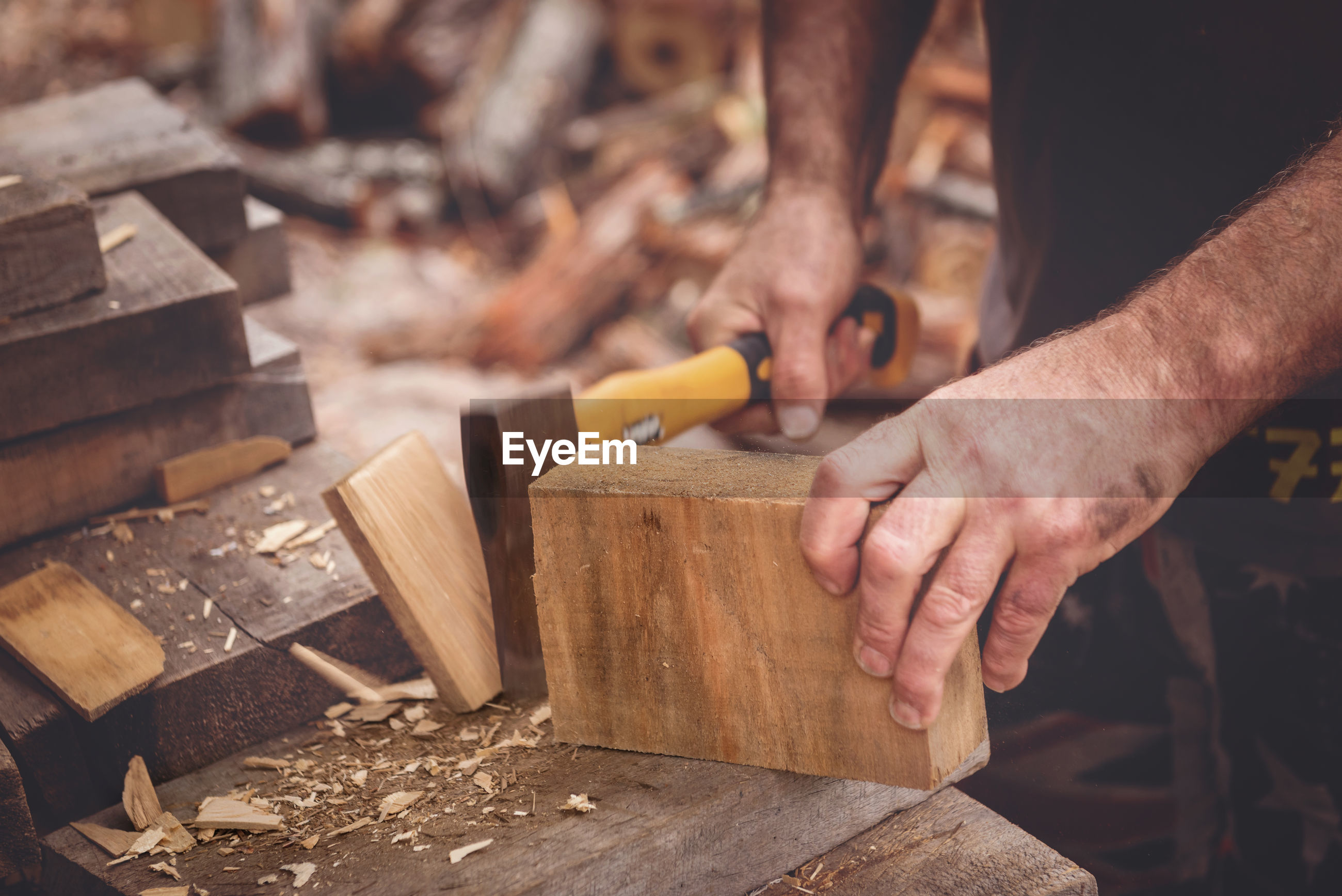 Midsection of carpenter cutting wood at workshop