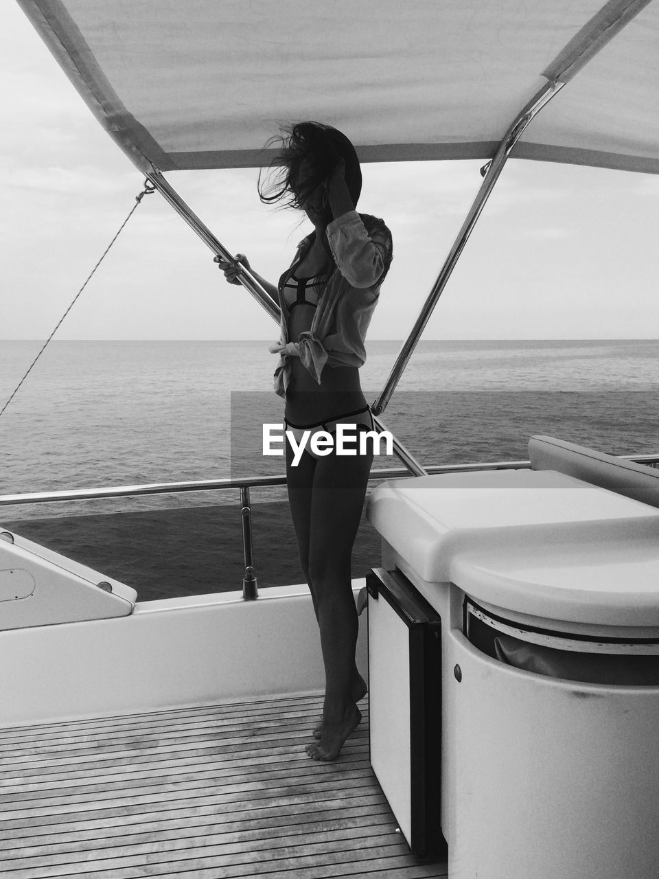 Young woman standing at boat deck on sea