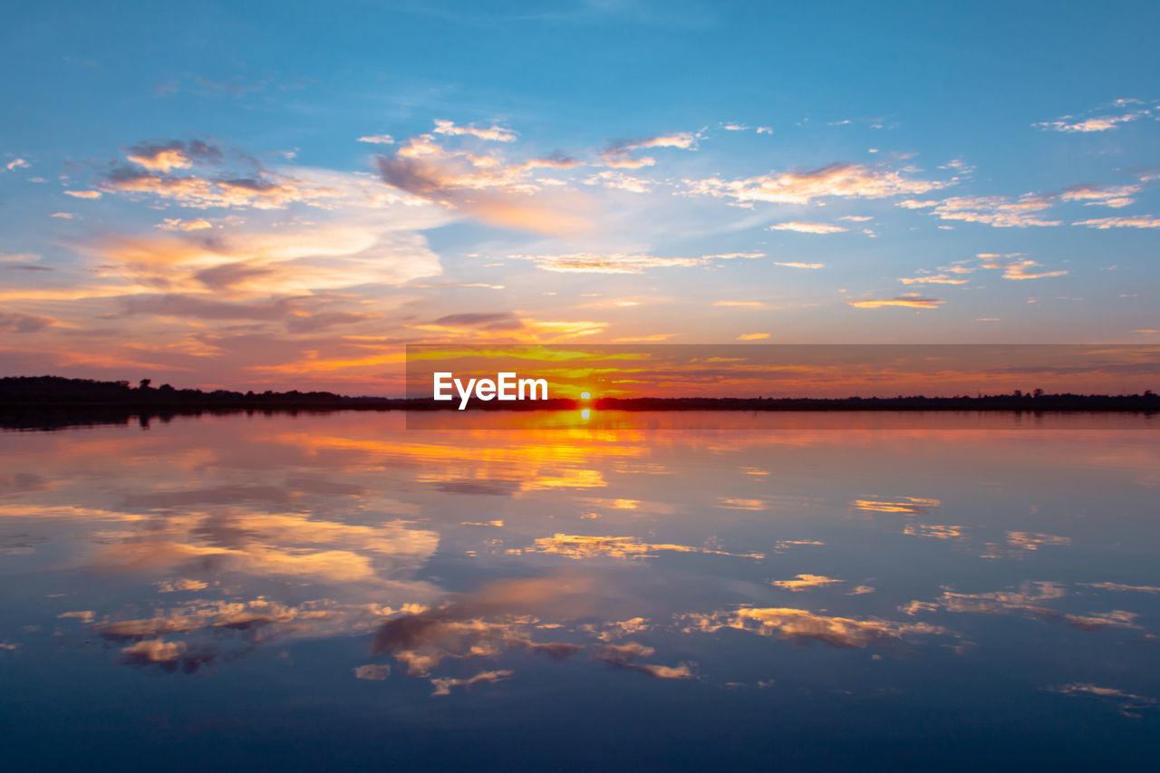 sky, sunset, cloud - sky, scenics - nature, beauty in nature, tranquility, water, tranquil scene, orange color, reflection, idyllic, nature, no people, waterfront, non-urban scene, lake, sunlight, symmetry, outdoors, salt flat, romantic sky