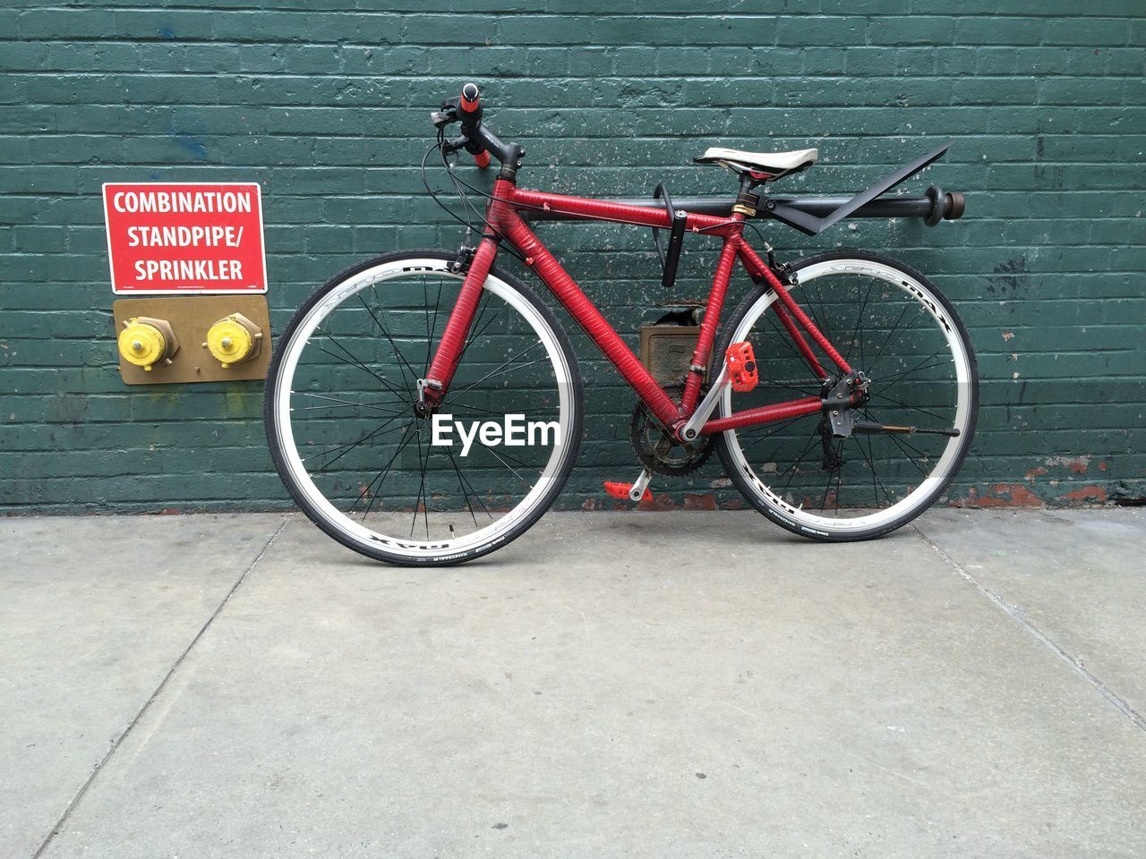 Side view of bicycle parked against the wall
