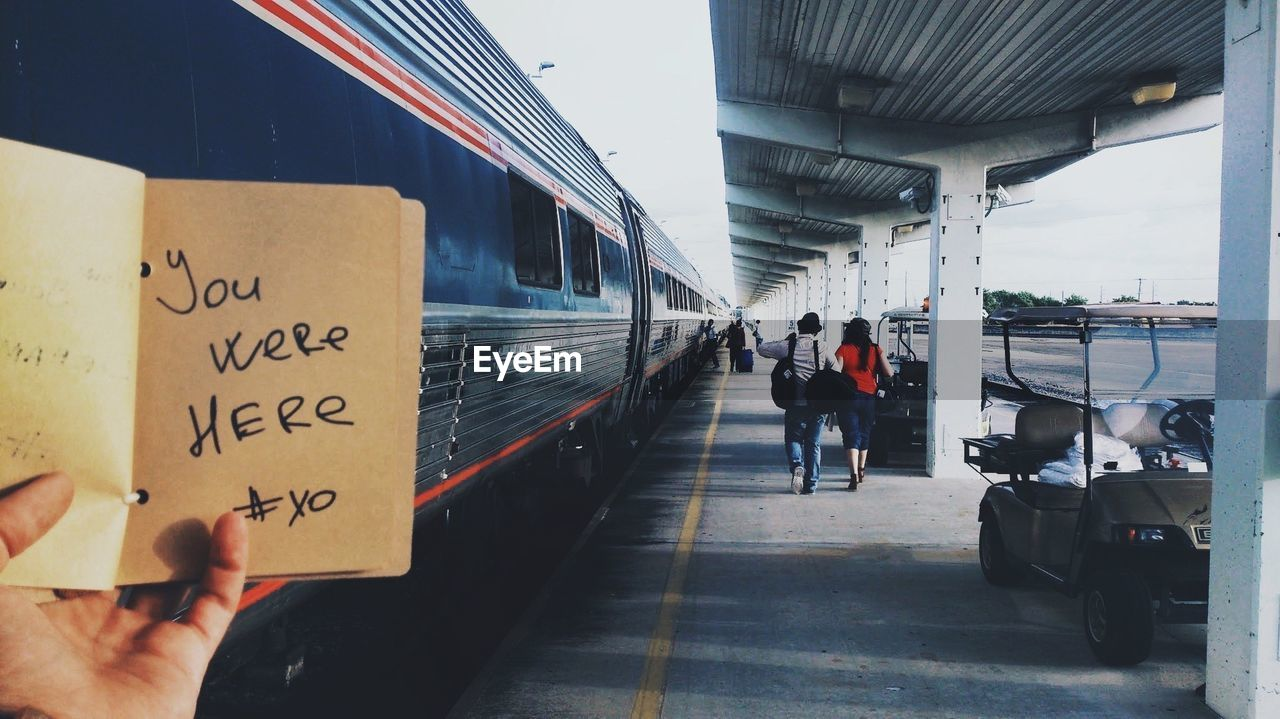 Cropped Image Of Person Holding Book With Text Written On It At Station