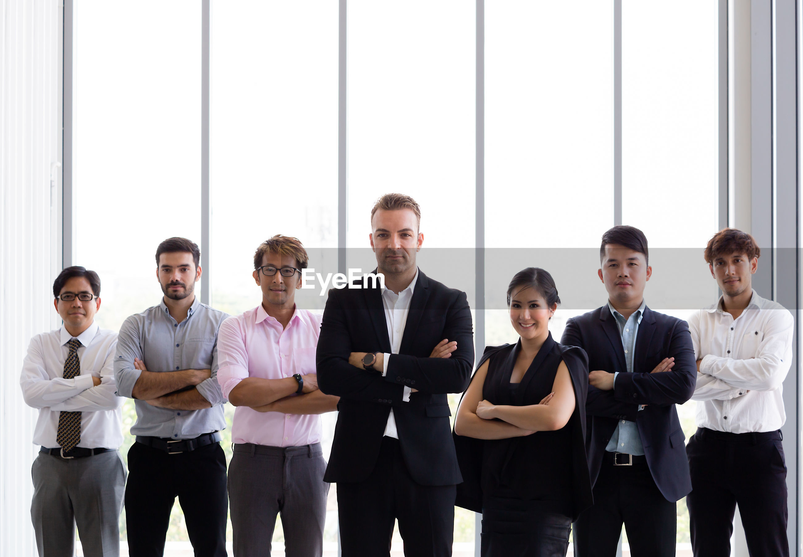 Portrait of confident business colleagues with arms crossed standing at office
